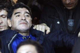Argentine former football player Diego Armando Maradona (L) looks on as he arrives on the stands during the Italian Cup semi-final second leg football match SSC Napoli vs AS Roma at the San Paolo Stadium in Naples, on February 12, 2014. AFP PHOTO/CARLO HERMANN