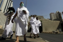 Muslim pilgrims walk to their buses as they prepare to leave the holy city of Mecca to Arafat, to mark the beginning of hajj in a day of prayer and supplication, in the Muslim holy city of Mecca, Saudi Arabia, Sunday, Oct. 13, 2013. This year some pilgrims are wearing masks as a precaution against the Middle East respiratory syndrome, which has stricken nearly 100 people, most of them in Saudi Arabia and the Middle East. The Saudi health minister, Abdullah al-Rabiah, said late Saturday that no cases of the coronavirus infection have been detected among pilgrims.