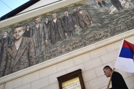 A man walks past a mural depicting Gavrilo Princip, the man who killed Austrian Archduke Franz Ferdinand one hundred years ago, and other members of 'Mlada Bosna' movement in the Bosnian Serb-run town of Visegrad, on June 28, 2014. Sarajevo on Saturday marks 100 years since the assassination that triggered World War I, plunging Europe into the bloodiest conflict it had ever seen and redrawing the world map. With the people of the Balkans still deeply divided over the legacy of that fateful day, separate commemorations were to be held to mark the occasion. AFP PHOTO / ANDREJ ISAKOVIC