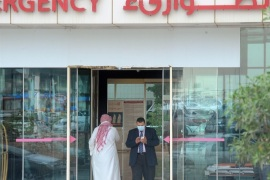 A man, wearing a mouth and nose mask, checks his phone as he leaves the hospital's emergency department on April 27, 2014 in the Saudi capital Riyadh. The MERS death toll in Saudi Arabia neared 100 this weekend as the authorities scrambled to reassure an increasingly edgy population in the country worst-hit by the infectious coronavirus. AFP PHOTO/FAYEZ NURELDINE