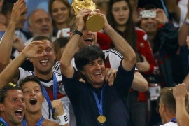 Germany's coach Joachim Loew lifts the World Cup trophy after his team won the 2014 World Cup final against Argentina at the Maracana stadium in Rio de Janeiro July 13, 2014. REUTERS/Kai Pfaffenbach (BRAZIL – Tags: SPORT SOCCER WORLD CUP)