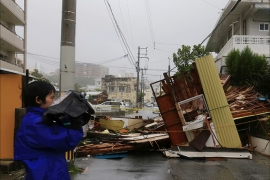 epa04305019 A reporter stands next to a wooden house hosting a restaurant obstructing a street after it collapsed due to the strong generated by typhoon Neoguri in Matsugawa district of Naha city, on the island of Okinawa, southern Japan, 08 July 2014. Residents on southern Japanese islands are advised to be on maximum alert early on 08 July 2014 as a powerful typhoon approached the region. The typhoon is expected to pick up more power before it makes landfall, the Japan Meteorological Agency said, as it issued an storm surge warning for Miyako Island in the southern prefecture of Okinawa and neighbouring islets.  EPA/HITOSHI MAESHIRO