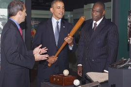 President Barack Obama, center, holds a bat belonging to Babe Ruth during a tour of the National Baseball Hall of Fame in Cooperstown, N.Y., on Thursday, May 22, 2014. With him are Hall of Fame president Jeff Idelson, left, and Andre Dawson, inducted into the Hall of Fame in 2010. (AP Photo/The Daily Star, Julie Lewis)
