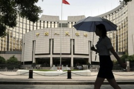 A woman walks past the headquarters of the People's Bank of China (PBOC), the central bank, in Beijing, in this file picture taken June 21, 2013. China's central bank is injecting a combined 500 billion yuan ($81.35 billion) of liquidity into the country's top banks, according to media reports, a sign that authorities are stepping up efforts to shore up a faltering economy REUTERS/Jason Lee/Files (CHINA – Tags: BUSINESS POLITICS)