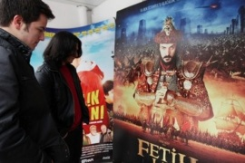 "Young Turks look at an advertisement for ""Conquest 1453"" displayed outside a cinema in Ankara, Turkey, Wednesday, Feb. 29, 2012. Turkey is on a roll these days, uplifted by economic growth and regional diplomacy. Now comes a film to boost the feel-good mood, an epic about the 15th century fall of Constantinople that fuses Turkish nationalism with Hollywood-style ambition. ""Fetih 1453,"" or ""Conquest 1453,"" casts good guys (read Muslim Ottomans) against bad guys (aka Christian Byzantines), transforming a clash of empires and religions into a duel between right and wrong."