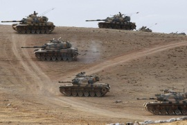 Turkish army tanks take up position on the Turkish-Syrian border near the southeastern town of Suruc in Sanliurfa province September 29, 2014. Turkish tanks and armoured vehicles took up positions on hills overlooking the besieged Syrian border town of Kobani on Monday as shelling by Islamic State insurgents intensified and stray fire hit Turkish soil, a Reuters correspondent said. At least 30 tanks and armoured vehicles, some with their guns pointed towards Syrian territory, were positioned near a Turkish military base just northwest of Kobani. Plumes of smoke rose up as shells hit the eastern and western sides of Kobani and sporadic bursts of machinegun fire rang out. REUTERS/Murad Sezer (TURKEY – Tags: POLITICS CONFLICT MILITARY TPX IMAGES OF THE DAY)