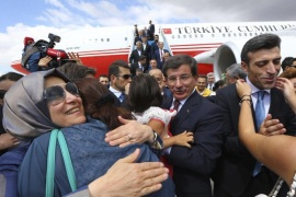 Turkish Consul General of Mosul Ozturk Yilmaz (2nd R) is welcomed by his relatives as Turkish Prime Minister Ahmet Davutoglu (C) looks on, as they arrive at Esenboga airport in Ankara September 20, 2014, in this handout courtesy of the Prime Minister's Press Office. Turkish intelligence agents brought 46 hostages seized by Islamic State militants in northern Iraq back to Turkey on Saturday after more than three months in captivity, in what President Tayyip Erdogan described as a covert rescue operation. Security sources told Reuters the hostages had been released overnight in the town of Tel Abyad on the Syrian side of the border with Turkey after being transferred from the eastern Syrian city of Raqqa, Islamic State's stronghold. The hostages, who included Yilmaz, diplomats' children and special forces soldiers, were seized from the Turkish consulate in Mosul on June 11 during a lightning advance by the Sunni insurgents. REUTERS/Hakan Goktepe/Prime Minister Press Office/Handout via Reuters (TURKEY – Tags: POLITICS CRIME LAW CIVIL UNREST TPX IMAGES OF THE DAY) ATTENTION EDITORS – THIS PICTURE WAS PROVIDED BY A THIRD PARTY. REUTERS IS UNABLE TO INDEPENDENTLY VERIFY THE AUTHENTICITY, CONTENT, LOCATION OR DATE OF THIS IMAGE. NO SALES. NO ARCHIVES. FOR EDITORIAL USE ONLY. NOT FOR SALE FOR MARKETING OR ADVERTISING CAMPAIGNS. THIS PICTURE IS DISTRIBUTED EXACTLY AS RECEIVED BY REUTERS, AS A SERVICE TO CLIENTS