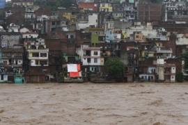 People watch the swelling River Tawi from the roof of their houses in Jammu, India, Saturday, Sept. 6, 2014. Heavy monsoon rains have caused flash floods and landslides that left more than 100 people dead in the disputed Himalayan region of Kashmir and in eastern Pakistan, officials said Friday. (AP Photo/Channi Anand)