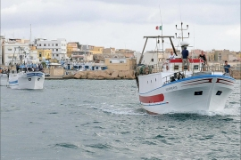 epa03897224 Boats leave Lampedusa harbor, Italy, on 05 October 2013 bringing local fishermen to the site off the coast where a vessel carrying migrants sank on 03 October. They were throwing a wreath to the waters off the Lampedusa island to pay a last respect to those who lost their lives in the most serious migrant boat accident in recent years. The provisional death toll on 04 October stood at 111 with 155 survivors and an unspecified number of people missing. EPA/ETTORE FERRARI