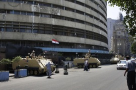 Egyptian military soldiers stand guard atop armored personnel carriers at Maspero, an Egypt's state tv and radio station, not far from Tahrir Square in Cairo Saturday, July 6, 2013. Egyptians were on edge Saturday morning after supporters and opponents of ousted President Mohammed Morsi fought overnight street battles that left at least 30 dead across the increasingly divided country.