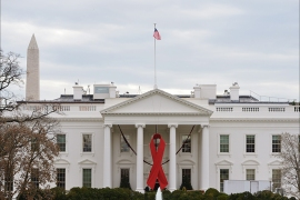 A giant red ribbon is affixed on the front of the White House on World Aids Day, on December 1, 2014 in Washington, DC. AFP PHOTO/Mandel NGAN