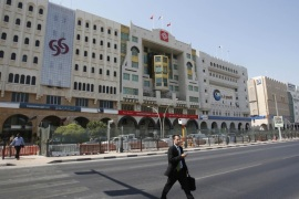 A man crosses the Grand Hamad street that hosts banks and financial institutions in Doha in this October 9, 2012 file photo. The year 2012 was transformational for global banks in the Middle East. Faced with a sharp slump in regional deal activity and pressure to save money, they reassessed their business models in a region that was once expected to become a key market for them, because of its oil and its sovereign wealth funds. To match story MIDEAST-BANKS/STRATEGY      REUTERS/Fadi Al-Assaad/Files  (QATAR – Tags: BUSINESS)