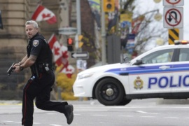 FILE – In this Wednesday, Oct. 22, 2014 file photo, an Ottawa police officer runs with his weapon drawn outside Parliament Hill in Ottawa.  Radical Muslim Michael Zehaf-Bibeau killed a soldier outside Canada's parliament. Right-wing extremist Larry McQuilliams opened fire on buildings in Texas' capital and tried to burn down the Mexican Consulate. Al-Qaida-inspired Michael Adebowale and an accomplice hacked an off-duty soldier to death in London. Police said the three perpetrators of recent attacks were terrorists and motivated by ideology. Authorities and family members said they may have been mentally ill. (AP Photo/The Canadian Press, Sean Kilpatrick, File)