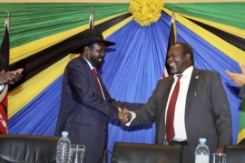 In this photo taken Wednesday, Jan. 21, 2015, South Sudan's President Salva Kiir, left, shakes hands with rebel leader and former vice president Riek Machar, right, after signing an agreement at the end of talks in Arusha, Tanzania. South Sudan's warring factions have agreed to reunify their political party, a conflict resolution organization said Thursday, with South Sudan President Salva Kiir and rebel leader Riek Machar signing the agreement to unite the ruling Sudan People's Liberation Movement on Wednesday in the Tanzanian town of Arusha, according to the Conflict Management Initiative. (AP Photo)