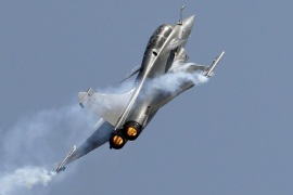 Rafale, a French fighter aircraft flies over static display area on the final day of Aero India air show at Yelahanka air base in Bangalore, India, Sunday, Feb. 22, 2015. Aero India is a biennial event with flying demonstrations by stunt teams and militaries and commercial pavilions where aviation companies display their products and technology. (AP Photo/Aijaz Rahi)