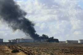 Black smoke billows out of a storage oil tank in the port of Es Sider in Ras Lanuf December 25, 2014. A rocket hit a storage tank at the eastern Libyan oil of port Es Sider as armed factions allied to competing governments fought for control of the country's biggest export terminal, officials said on Thursday. REUTERS/Stringer (LIBYA – Tags: CIVIL UNREST POLITICS TPX IMAGES OF THE DAY)