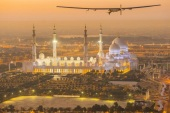 The Solar Impulse 2, a solar-powered plane, flies over the Sheikh Zayed Grand Mosque in Abu Dhabi during preparations for next month's round-the-world flight, February 26, 2015. Swiss pilots Bertrand Piccard and Andre Borschberg will attempt to fly around the world in the Solar Impulse 2, in a bid to prove that such a flight is possible without the use of fossil fuels. The solar-powered plane has a wingspan of 72 metres, larger than that of a Boeing 747, but weighs only 2.3 tons, about as much as a family car. More than 17,000 solar cells on the wing power lithium-ion batteries in four electric motors. The airframe makes use of carbon fiber, which is three times lighter than paper, to keep the plane as light as possible. The 35,000 km flight is expected to take about five months, with stops in Oman, India, Myanmar, China, the United States, and in Southern Europe or North Africa depending on the weather. The Solar Impulse 2 is expected to land back in Abu Dhabi in late July or early August.     REUTERS/Solar Impulse/Revillard/Rezo.ch/Handout via Reuters (UNITED ARAB EMIRATES)ATTENTION EDITORS – THIS PICTURE WAS PROVIDED BY A THIRD PARTY. REUTERS IS UNABLE TO INDEPENDENTLY VERIFY THE AUTHENTICITY, CONTENT, LOCATION OR DATE OF THIS IMAGE. NO SALES. NO ARCHIVES. FOR EDITORIAL USE ONLY. NOT FOR SALE FOR MARKETING OR ADVERTISING CAMPAIGNS. THIS PICTURE IS DISTRIBUTED EXACTLY AS RECEIVED BY REUTERS, AS A SERVICE TO CLIENTS
