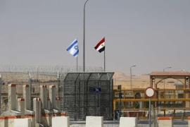 An Israeli flag (L) flutters next to an Egyptian one at the Nitzana crossing, along Israel's border with Egypt's Sinai desert, as seen from the Israeli side August 20, 2013. Egypt began three days of official mourning for 25 policemen killed on Monday by suspected Islamist militants in the Sinai near the desert border with Israel. REUTERS/Ronen Zvulun (ISRAEL – Tags: POLITICS)