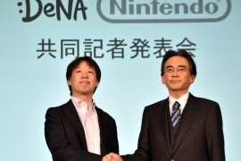Japan's video game giant Nintendo president Satoru Iwata (R) shakes hands with Japanese online game operator DeNA president Isao Moriyasu during a press conference in Tokyo on March 17, 2015. Nintendo said on March 17 it was teaming up with a mobile gaming company to develop games for smartphones in what could be a turning point for the Japanese giant which has long refused to enter the soaring market.  AFP PHOTO / Yoshikazu TSUNO