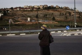 A Jewish settler woman waits for a ride outside the Jewish West Bank settlement of Shilo, background, Wednesday, Feb. 22, 2012. Israel gave preliminary approval on Wednesday to a plan to build 600 new homes in a settlement deep inside the West Bank, a move that drew a rebuke from the United Nations and Palestinians and threatened to raise new tensions with the U.S. as the prime minister prepares to head to the White House.