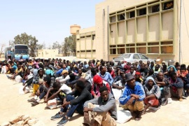 Migrants from sub-Saharan Africa sit at a center for illegal migrants in the al-Karem district of the Libyan eastern port city of Misrata on May 9, 2015, as they wait to be transported to a different detention center. Mohammed Khalifa al-Guwail, the acting prime minister of Libya's disputed government, urged European Union countries to help his administration tackle illegal immigration by sending boats for the coastguard. AFP PHOTO / MAHMUD TURKIA