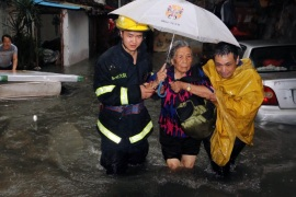 SHA4721 – Xiamen, Fujian, CHINA : This picture taken on May 20, 2015 shows rescuers helping a resident through a flooded area during an intense rainstorm that killed 7 people in Xiamen, east China's Fujian province. Rainstorms have lashed large swathes of south and central China since May 17, affecting more than a million and leaving at least 15 dead and seven missing, state media reported. AFP PHOTO CHINA OUT