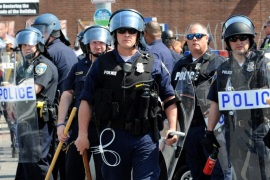 Police guard an intersection Monday, May 4, 2015, in Baltimore. Lt. Col. Melvin Russell said police pursued a man who was spotted on surveillance cameras and appeared to be armed with a handgun. Police said the man was taken into custody after a brief chase, during which a gunshot was heard. (Algerina Perna/The Baltimore Sun via AP)