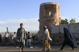 Residents walk past as Afghan security forces inspect the scene of a suicide attack on a police headquarters in Jalalabad, Afghanistan June 1, 2015. Taliban militants stormed the police headquarters after a suicide bomb attack at its gate and wounded at least nine policemen, officials said on Monday. REUTERS/PARWIZ