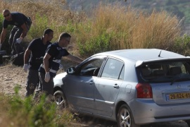 Israeli forensic police inspect a car belonging to Israeli victims of a gun attack by a Palestinian man near the Dolev settlement, northwest of Ramallah in the Israeli-occupied West Bank, on June 19, 2015. A Palestinian opened fire on two Israeli men, killing one and wounding the other, according to the Israeli authorities, in what appeared to be yet another lone-wolf attack. AFP PHOTO / ABBAS MOMANI