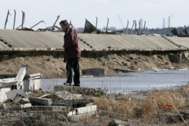 A man is standing on basement of a house destroyed by tsunami at Ukedo in Namie, about five km north of tsunami-crippled Tokyo Electric Company's Fukushima Daiichi Nuclear Power Plant (seen in right rear), Fukushima Prefecture, northern Japan, 10 March 2015, the eve of fourth anniversary of the March 11 earthquake and tsunami in 2011. Namie town, close to Fukushima Daiichi Nuclear Power Plant, had the largest number of such deaths at 359. The plant suffered a triple meltdown caused by the March 11, 2011 earthquake and tsunami that left about 18,500 dead.
