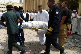 Kuwaiti security personnel and medical staff carry a man on a stretcher at the site of a suicide bombing that targeted the Shiite Al-Imam al-Sadeq mosque after it was targeted by a suicide bombing during Friday prayers on June 26, 2015, in Kuwait City. The Islamic State group-affiliated group in Saudi Arabia, calling itself Najd Province, said militant Abu Suleiman al-Muwahhid carried out the attack, which it claimed was spreading Shiite teachings among Sunni Muslims. AFP PHOTO / STR