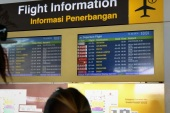 Passengers look at the information board in the international terminal at Bali's Ngurah Rai airport in Denpasar hoping for information of flight delays due to volcanic ash near Indonesia's resort island on July 10, 2015. Ash drifting from an Indonesian volcano closed five airports on July 10, including the one on the holiday island of Bali, causing about 250 flights to be cancelled and stranding thousands of holidaymakers. The international airport on nearby popular Lombok island was also among those closed late on July 9 as Mount Raung in East Java province spewed clouds of ash.      AFP PHOTO / SONNY TUMBELAKA