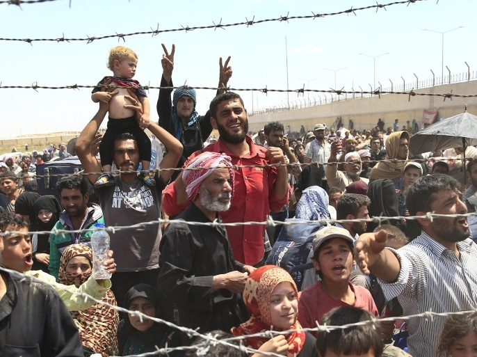 FILE – In this Monday, June 15, 2015 file photo, Syrian refugees gather at the Turkish border as they flee intense fighting in northern Syria between Kurdish fighters and Islamic State militants in Akcakale, southeastern Turkey. (AP Photo/Lefteris Pitarakis, File)
