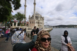 Tourists take pictures at the Ortakoy square in Istanbul, Turkey, backdropped by the Ottoman-era Mecidiye mosque and the Bosporus Bridge, Sunday, June 7, 2015. Turkey is heading to the polls on Sunday in a crucial parliamentary election that will determine whether ruling party lawmakers can rewrite the constitution to bolster the powers of Erdogan.  (AP Photo/Lefteris Pitarakis)