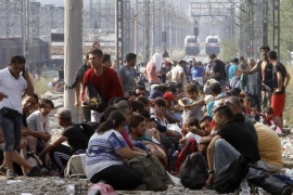 Migrants wait to enter Macedonia from Greece on the border line between the two countries, near the southern Macedonian town of Gevgelija, Wednesday, Aug. 26, 2015. Thousands of migrants have poured into Macedonia to board trains and buses taking them a step closer to the European Union. The new surge of migrants has worried EU politicians and left the impoverished Balkan countries struggling to cope with the humanitarian crisis. (AP Photo/Boris Grdanoski)