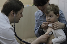 In this Monday, April 23, 2013 photo pediatrician Fyodor Lapiy examines a child before administering him a combined vaccine against diphtheria, whopping cough and tetanus  in Children's Hospital No. 1 in Kiev,Ukraine. Only about one-half of Ukraine s children are fully immunized against vaccine-preventable communicable diseases in line with local health regulations, compared to over 90 percent in Western Europe, according to UNICEF, the United Nations children s agency. Such a low immunization rate has already led to a major outbreak of measles and a risk of an outbreak of polio, a highly dangerous disease which may cause paralysis and which has been unseen in Ukraine for more than a decade, UNICEF and the World Health Organization said ahead of the current World Immunization week.