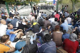 Migrants wait at the Horgos 2 border crossing at the Serbia-Hungary border, 15 September 2015. Hungary has sealed the last gap in the barricade along its border with Serbia, closing the passage to thousands of refugees and migrants still waiting on the other side.
