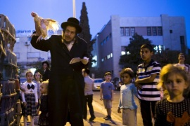 An ultra-Orthodox Jewish man holds a chicken as he does the Kaparot ritual ahead of Yom Kippur, the Jewish Day of Atonement, which starts at sundown on Tuesday, in the southern city of Ashdod, Israel September 20, 2015. Kaparot is an ancient custom connected to Yom Kippur, where white chickens are slaughtered as a symbolic gesture of atonement. REUTERS/ Amir Cohen