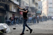 A Palestinian protesters throws stones during clashes with members of the Israeli armed forces in the West Bank city of Hebron, 09 October 2015. Israeli soldiers killed four Palestinians in clashes on the border with the Gaza Strip, while there were four stabbing incidents inside Israel targeting both Jews and Palestinians. Violence has been ongoing for weeks, focused on Jerusalem and nearby areas on the West Bank amid rising concerns the situation could lead to an even greater escalation if not scaled back soon.