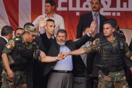FOR USE AS DESIRED, YEAR END PHOTOS – FILE – In this June 29, 2012 file photo, Egypt's President-elect Mohammed Morsi waves to supporters after giving a speech at Tahrir Square in Cairo.  (AP Photo/Khalil Hamra, File)