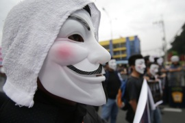 "Filipino student protesters wearing masks are blocked by police as they tried to get near the House of Representatives in suburban Quezon city, north of Manila, Philippines on Tuesday Nov. 5, 2013. Supporters of hacker group Anonymous Philippines held the rally to call for the abolition of all forms of ""pork barrel"" funds after allegations that several members of the House of Representatives and the Philippine Senate conspired with wealthy businesswoman Janet Lim Napoles to steal huge amounts of government development funds. Napoles is set to appear before the Senate Blue Ribbon Committee on Nov. 7. (AP Photo/Aaron Favila)"