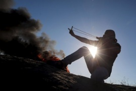 A Palestinian protester uses a slingshot to hurl stones towards Israeli troops during clashes near the border between Israel and Central Gaza Strip October 30, 2015. Knife-wielding Palestinians attacked Israelis in Jerusalem and the Israeli-occupied West Bank on Friday and one assailant was shot dead, police said, extending a wave of violence spurred in part by tensions over a Jerusalem holy site. REUTERS/Ibraheem Abu Mustafa