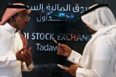 Traders talk as they monitor screens displaying stock information at the Saudi Stock Exchange (Tadawul) in Riyadh June 15, 2015. The chief executive of Saudi Arabia's stock exchange said on Monday he expected a flurry of licenses allowing the first foreign investors to buy shares there in coming weeks. To match Interview SAUDI-STOCKEXCHANGE/   REUTERS/Faisal Al Nasser