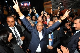 "Former Tunisian president Moncef Marzouki (C) flashes the sign for victory amid his supporters during a rally to launch his new political party Al-Irada (the will) in the capital Tunis on December 20, 2015. Marzouki, a 70-year-old neurologist and founder of the Congress for the Republic party during Ben Ali's long dictatorship, has warned of a ""catastrophic"" situation in his country, plagued by poverty and jihadists, as he launched a new party a year after his election defeat. AFP PHOTO / FETHI BELAID"