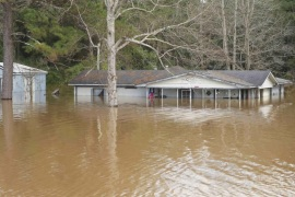 A house is under water on the banks of the Pea River in Elba, Alabama, December 26, 2015.  Alabama has been hit with storms and heavy rain since Wednesday, and the Weather Service issued flash flood warnings around the region for Friday.  REUTERS/Marvin Gentry