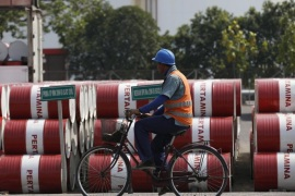 An employee rides his bike past barrels of petroleum products at a state-owned Pertamina fuel depot in Jakarta September 9, 2014. Indonesia's main anti-graft watchdog is planning a sector-wide audit of the country's oil and gas industry next year, the latest step in a push to clean up the energy sector and restore investor confidence in Southeast Asia's biggest crude producer.   Photo taken on September 9, 2014.    REUTERS/Darren Whiteside (INDONESIA) – Tags: CRIME LAW BUSINESS ENERGY)