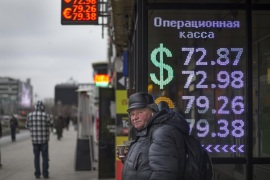 A man warms himself with a cup of hot coffee by an exchange office sign showing the currency exchange rates of the Russian ruble, U.S. dollar, and euro in Moscow, Russia, Wednesday, Dec. 30, 2015. The Russian ruble dropped 1.3 percent in early morning trading on Wednesday to 73.2 rubles, its lowest level in a year. The national currency lost 40 percent of its value last year and is now 20 percent down compared to a year ago.  (AP Photo/Alexander Zemlianichenko)
