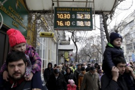 People walk past a board showing currency exchange rates of foreign currencies against the Russian rouble in the southern city of Krasnodar Russia, December 19, 2015. REUTERS/Eduard Korniyenko
