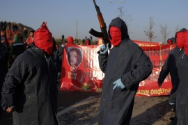 Masked and armed men walk during funeral of Sirin Oter and Yeliz Erbay, two women killed during security operations on Tuesday, in Istanbul, Wednesday, Dec. 23, 2015. Security forces have killed 145 Kurdish rebels in a week in southeast Turkey, news agencies reported. The government imposed curfews in the mainly Kurdish towns of Cizre, Silopi and Sur as the security forces battle militants linked to the Kurdistan Workers' Party, or PKK who have moved their fight for autonomy to some towns and city neighborhoods in southeastern Turkey. (AP Photo/Emrah Gurel)