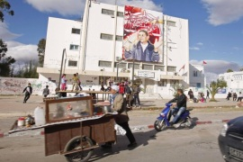 People walk past a large placard on a building featuring Mohamed Bouazizi on the fourth anniversary of his death in Sidi Bouzid December 17, 2014. Bouazizi was a Tunisian street vendor who set himself on fire on December 17, 2010, which led to the ousting of President Zine El Abidine Ben Ali 28 days later on January 14, 2011.  REUTERS/Zoubeir Souissi (TUNISIA – Tags: POLITICS SOCIETY)